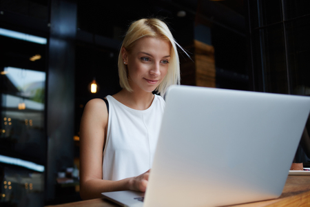 coursework: Beautiful young blonde female student using portable laptop computer while work at the coursework, woman sitting at the table with open net-book in coffee shop interior during morning breakfast Stock Photo