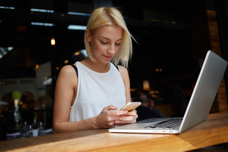 prettiness: Beautiful lady chatting on smart phone while sitting at the table with laptop computer in cafe bar interior, pretty European woman using cell telephone while relaxing after work on portable net-book Stock Photo