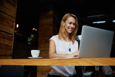 Pretty female student with cute smile keyboarding something on net-book while relaxing after lectures in University, beautiful happy woman working on laptop computer during coffee break in cafe bar