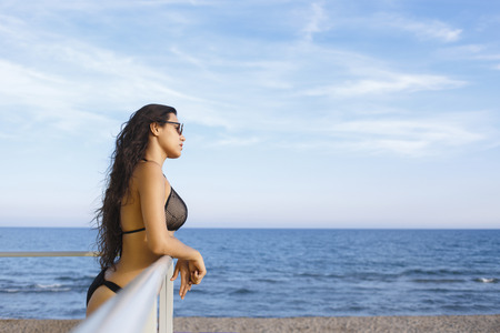 Portrait of a young dreamy women with sexy body enjoying sea landscape while sunbathing on the beach, thoughtful Lain female in bikini resting after swimming on the ocean during her recreation time