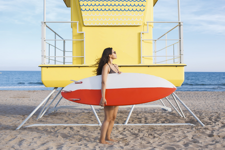 bronzed: Full length portrait of women holding surfboard with copy space for your brand while standing near lifeguard house on the beach, young female preparing for surfing in beautiful sunny summer day