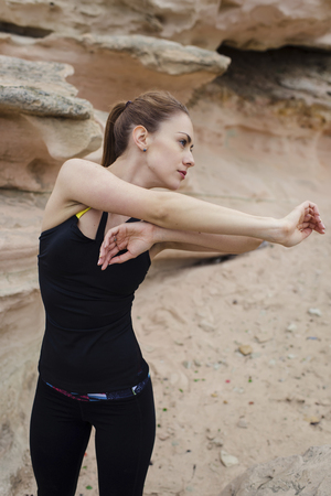 half dressed: Half length portrait of young female jogger dressed in sport wear doing arms stretching exercise outdoors in nature landscape, fit caucasian woman with perfect body working out in stone rock mountains