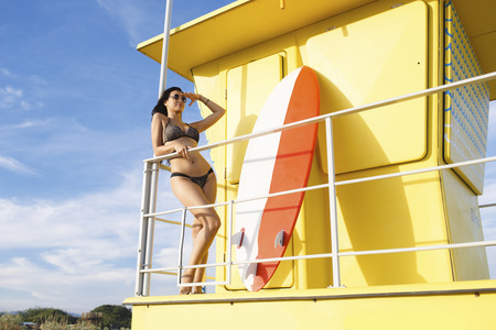 area sexy: Portrait of a young women with hand near forehead looking away from lifeguard house while resting after surfing, charming surfer female in bikini relaxing after swimming in the sea in sunny summer day Stock Photo