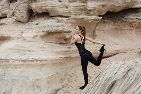 activewear: Portrait of a young female jogger stretches legs muscles before a fitness training on the fresh air outside, charming sports woman with beautiful figure working out outdoors in mountain landscape