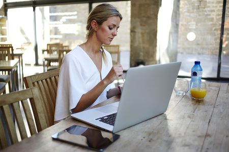 netbook: Portrait of a young beautiful elegant women relaxing after work on portable laptop computer during coffee break, female freelancer sitting at the wooden table with her net-book and digital tablet Stock Photo