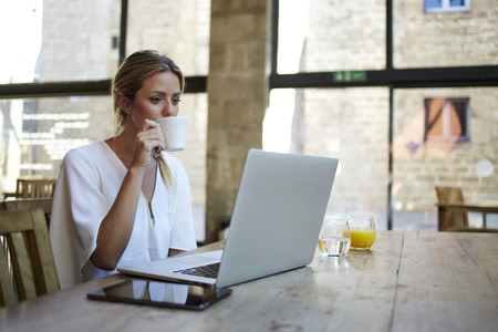 Portrait of a young beautiful businesswomen enjoying coffee during work on portable laptop computer, charming female student using net-book while sitting in cafe bar interior during morning breakfast