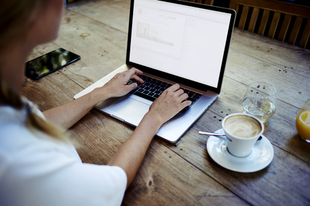 フロントのラップトップ コンピューターについては、若いビジネス女性仕事ネット予約で朝食時に現代のコーヒー ショップで空白のコピー スペー