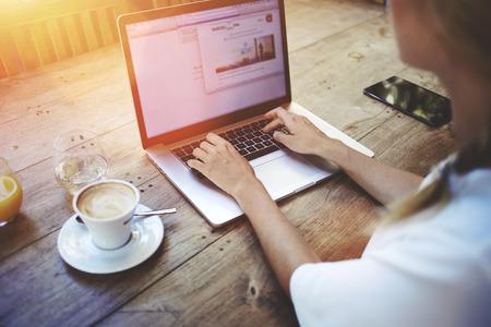 cafe internet: Ver Recortar foto de joven estudiante inteligente de aprendizaje en línea a través del ordenador portátil antes de sus conferencias, mujer inteligente sentado delante arco-libro con pantalla de espacio de la copia para su mensaje de texto Foto de archivo