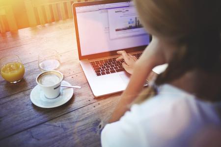 金髪女性フリーランスのコンピューター経由でインターネットに接続する屋内では、コーヒー ショップに座ってネット書籍に取り組んでいる若い女