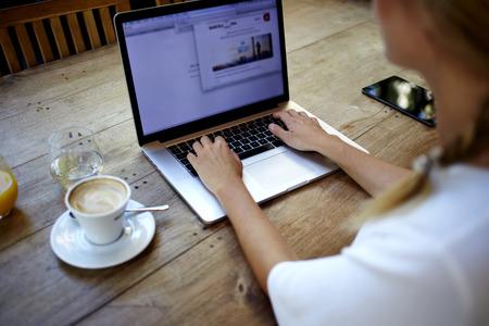 Vue arrière du jeune réussie utilisation de pigiste femme net-book pour le travail à distance pendant son temps de loisirs, les mains de la dactylographie de la femme sur ordinateur portable portable avec copie espace vide de l'écran Banque d'images
