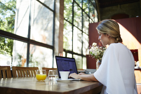coursework: Portrait of a young female student using portable laptop computer while work at the coursework, blonde woman sitting at the table with open net-book in coffee shop interior during morning breakfast
