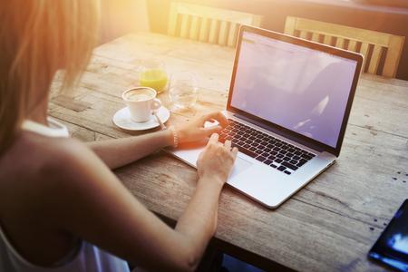 gente exitosa: Ver Recortar foto de joven mujer de mecanografía en el ordenador portátil con pantalla en blanco espacio de la copia mientras se está sentado en el café, estudiante rubia que trabaja en red-libro después de sus conferencias en la Universidad, la flama del sol