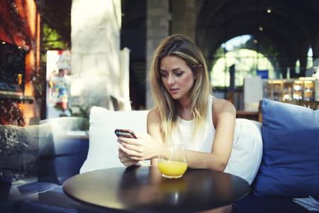 cafe internet: Retrato de una mujer linda rubia leer algo en su teléfono inteligente mientras está sentado en la cafetería moderna, hermosa chica inconformista joven que usa el teléfono celular mientras disfruta de su tiempo libre en el café caro