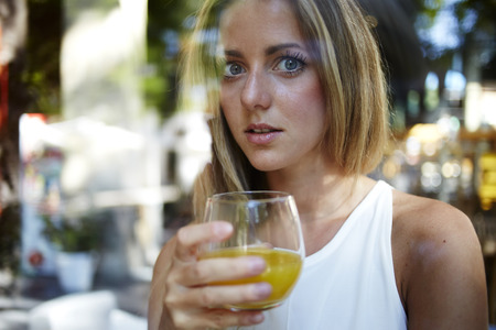 sweden resting: View though the window of a attractive female drinking a glass of fresh orange juice, young happy caucasian woman enjoying natural and vitamin beverage in home, gorgeous girl refresh with useful drink