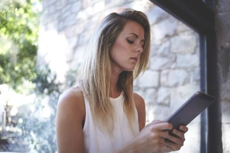 big window: Portrait of a young beautiful blonde women reading electronic book on her digital tablet while standing near big window in office space, charming Sweden female using touch pad during work break
