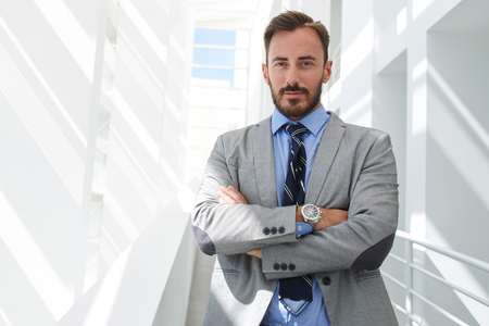 Half length portrait of a young handsome businessman with crossed arms standing in white hallway of his company, confident man managing director dressed in suit posing while resting after conference