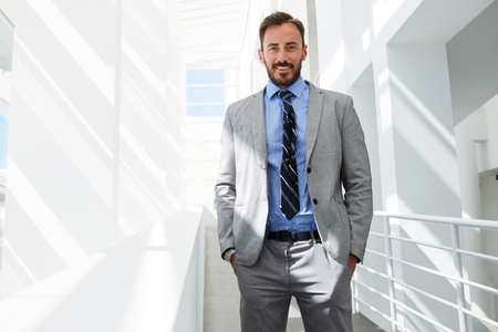half dressed: Half length portrait of a happy smiling successful men manager posing while standing on the corridor of office building, cheerful smart businessman dressed in elegant suit resting after conference
