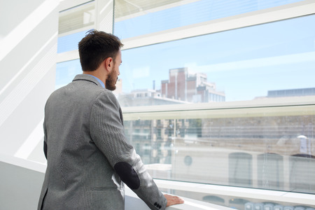 hard day at the office: Back view of a young businessman thinking about something while looking in big office window, confident serious men managing director dressed in formal wear enjoying calm after hard work day