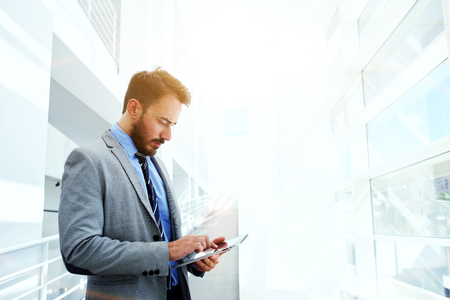 lifestyle caucasian: Half length portrait of handsome businessman concentrated watching in touch pad while standing in hallway of his company, young successful intelligent male in suit use digital tablet during work break Stock Photo