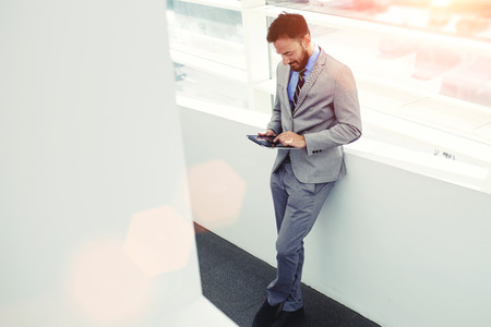 young handsome man: Full length portrait of a young successful man entrepreneur dressed in elegant clothes using touch pad, intelligent male professional worker holding digital tablet while resting after business meeting