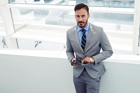 Portret van een jonge knappe man beambte stellen terwijl status met touch pad in het moderne kantoor interieur, zelfbewuste man boos gekleed in bedrijfskleding met behulp van digitale tablet tijdens het werk pauze