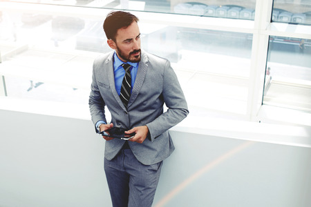 rich life: Portrait of young male professional worker dressed in corporate clothing holding touch pad while standing in office building, successful man entrepreneur dressed in elegant suit using digital tablet