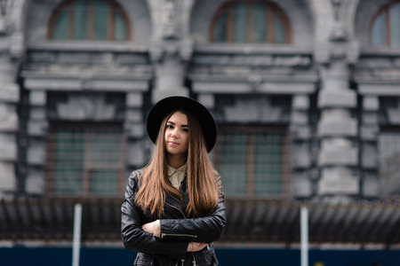 half dressed: Half length portrait of charming woman dressed in stylish clothes posing outdoors in cool spring day, attractive female standing with crossed arms on the street, glamorous hipster girl looking at you Stock Photo
