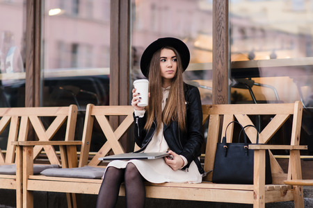 mujer bonita: Stylish charming hipster girl thoughtfully looks aside while resting after work on laptop computer, young female student holding closed net-book on knee while sitting with cup on coffee on the street Foto de archivo