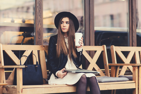 well dressed girl: Portrait of a glamorous young woman holding on her knees portable laptop computer while sitting on a wooden bench, stylish female drinking coffee while relaxing after work on net-book during free time