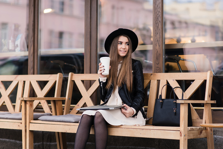 prettiness: Funky woman with cool style holding closed net-book on her knees while sitting on a cozy bench near coffee shop window, young hipster girl enjoying c while resting after work on laptop computer Stock Photo