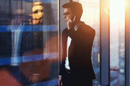 Portrait of successful businessman talking on mobile phone while standing against window in hallway of modern office interior, young confident man having cell telephone conversation during work break Stock Photo