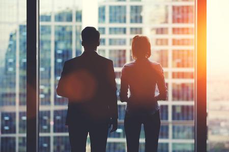 liderazgo empresarial: Volver la vista siluetas de dos socios de negocios que mira cuidadosamente fuera de una ventana de la oficina en situación de quiebra, el equipo de empresarios en el miedo o el riesgo de ver el paisaje urbano del interior rascacielos