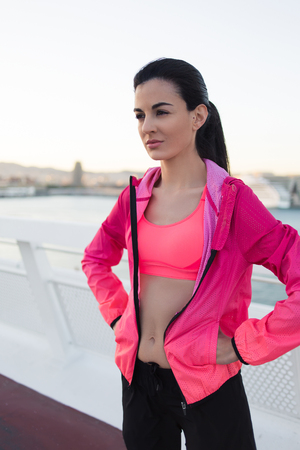 half dressed: Half length portrait of young beautiful woman dressed in bright tracksuit taking break after workout out, charming and fit female runner with slim body relaxing after evening jog outdoors in summer Stock Photo