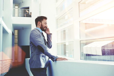 Half length portrait of young successful business man having cell telephone conversation while standing in office interior, male professional banker in suit talking on mobile phone during work break