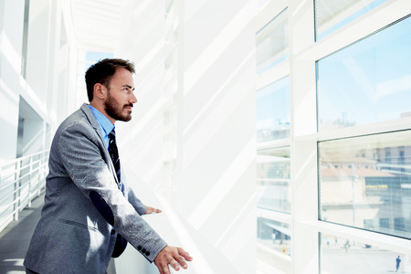 Portrait of a serious man office worker dressed in elegant clothes watching in window while standing in modern office space, thoughtful young male entrepreneur in suit resting after business meeting Foto de archivo