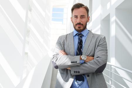 Portré, fiatal, intelligens ember ügyvéd állt keresztbe fegyver modern irodaház belső, sikeres férfi banki alkalmazott öltözött luxus ruha jelentő másolatot tér területe a szöveg