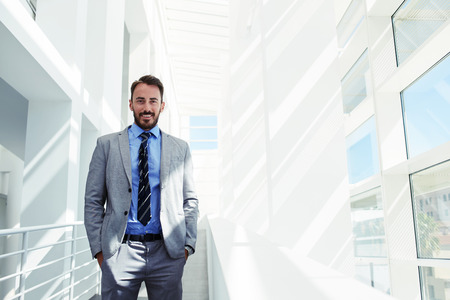 economist: Half length portrait of young smiling men entrepreneur dressed in luxury suit with hands in pockets standing in modern office interior, handsome happy prosperous economist  posing with copy space area Stock Photo