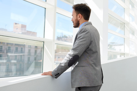 formal wear: Back view of young successful businessman thinking about something while looking in big office window, confident serious men managing director dressed in formal wear enjoying calm after hard work day Stock Photo