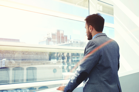 wealthy lifestyle: Back view of a young men entrepreneur thinking about something while looking in big office window, successful serious businessman dressed in elegant luxury clothes enjoying calm after hard work day Stock Photo