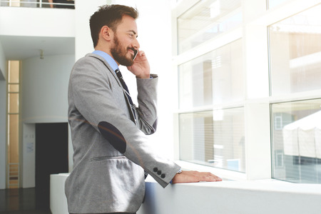 financier: Smiling successful man financier dressed in luxury clothes talking on his mobile phone while standing in modern office, young cheerful businessman having cell telephone conversation with copy space