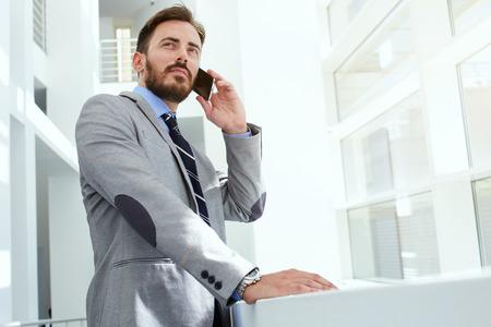 Fele hossza portré egy intelligens ember ügyvéd hívja a mobiltelefonjára állva modern irodaterület, fiatal magabiztos férfi vállalkozó beszél okostelefonok míg pihenés után találkozó