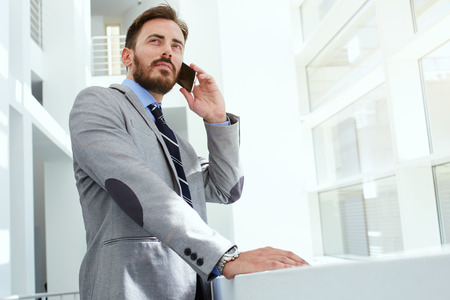 Half length portrait of a intelligent man lawyer calling with cell telephone while standing in modern office space, young confident male entrepreneur speaking on smart phone while rest after meeting Stock Photo