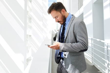 half dressed: Half length portrait of a handsome businessman dressed in luxury suit using mobile phone while resting after briefing, young smart male lawyer reading something on cell telephone, copy space area Stock Photo