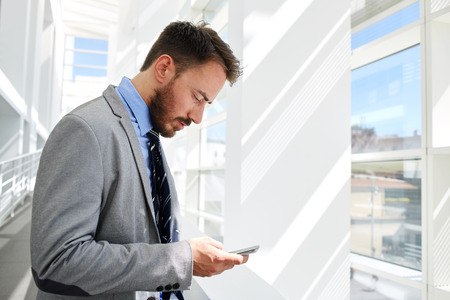 financier: Young male financier chatting on cell telephone before business meeting with his partners, confident man ceo dressed in formal wear reading message on mobile phone while standing in office hallway