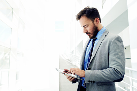 lifestyle caucasian: Portrait of a confident men entrepreneur dressed in expensive suit working on digital tablet while standing in modern office interior, intelligent male lawyer working on touch pad during work break