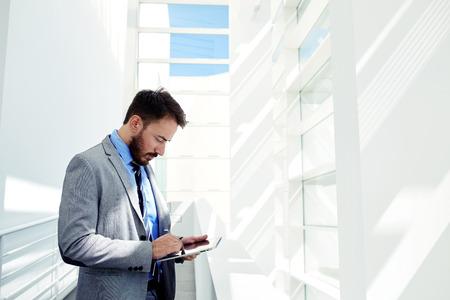 hombres trabajando: La mitad retrato de cuerpo del varón joven director gerente usa la pista de tacto en la oficina moderna con inter copia del espacio, hombre de negocios experto vestido con elegante ropa de trabajo corporativos en la tablilla digital Foto de archivo