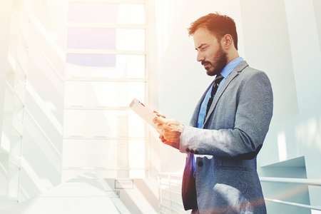 economist: Portrait of young confident man economist holding digital tablet while standing in modern office corridor, male managing director dressed in luxury corporate clothes working on touch pad during break Stock Photo