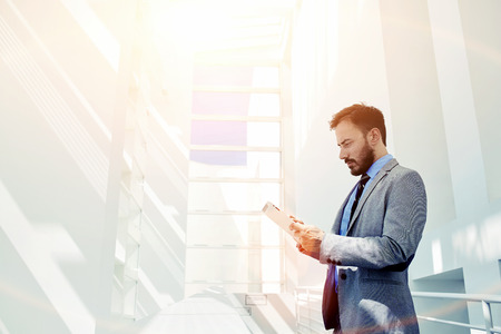 Fele hossza portré egy férfi ügyvéd öltözött szürke luxus öltöny gazdaság touch pad állva modern belső nagy vállalat, benne pénzember digitális tábla munka közben szünet