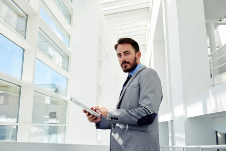 financier: Half length portrait of a young purposeful male lawyer dressed in suit working on touch pad during work break, smart male financier in corporate clothes using digital tablet to prepare for the meeting Stock Photo