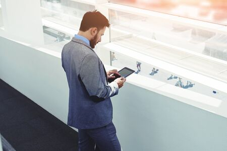 purposeful: Portrait of a young man professional banker working on touch pad while standing in modern office space interior,purposeful male entrepreneur dressed in luxury clothes use digital tablet before meeting